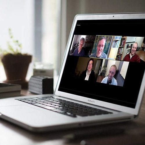 laptop sitting on a table by a window, the screen shows a video meeting